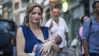 Một phụ nữ Hy Lạp bồng con nhỏ đi dự lễ hội tôn thờ các vị thần ở chân Đỉnh Olympus.