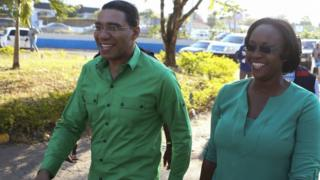 Andrew Holness (L), leader of the opposition Jamaican Labour Party, arrives with his wife Juliet, to cast his vote at a polling station during general election in Kingston, Jamaica February 25, 2016.
