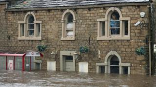 People look out from their windows and are trapped by flood water as the River Calder bursts its bank's in Mytholmroyd, England.