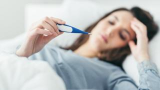 Woman in bed with thermometer (Posed by model)