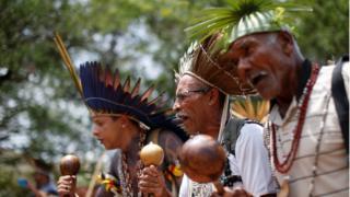 Indígenas de várias tribos dançam enquanto esperam para entregar uma carta ao presidente eleito Jair Bolsonaro, em dezembro