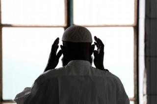 A man wearing a small cap, called the taqiyah, faces a window as he raises his hands either side of his head in prayer.