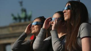 People use special glasses to look into the sky at a partial solar eclipse near the Brandenburg Gate on March 20, 2015 in Berlin