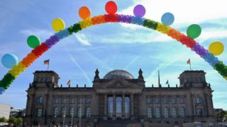 A balloon chain in rainbow colours is seen in front of the Reichstag building housing the German parliament as activists of the LGBT movement demonstrate against homophobia. Photo: 17 May 2017