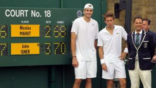 Isner and Mahut pose with the scoreboard after their marathon match at Wimbledon