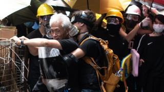 Протестувальники тримають депутата від опозиції, який закликав їх до порядку
