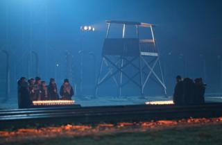 Mike Pompeo Participants stand at candles near the railroad tracks and an illuminated guard tower at the former Auschwitz-Birkenau concentration camp during the official ceremony to mark the 75th anniversary of the liberation of the camp.