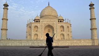 2013 file photo of worker sweeping in front of Taj Mahal in Agra, India