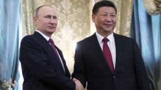 El presidente de Rusia, Vladimir Putin, estrecha la mano de su homólogo chino, Xi Jinping.