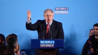 Boris Johnson at podium delivering speech at QE2 centre in central London