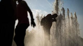 A man cools himself with water in a fountain at Lustgarten park in Berlin,