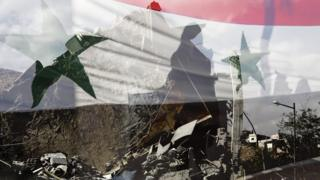 Syrian flag overlaid on rubble