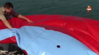 Coastguards deflate a water trampoline