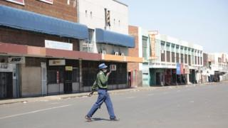A woman walks on on an deserted street and closed shops, a day before anti government protests, in the central business district of Harare, Zimbabwe, 30 July 2020.