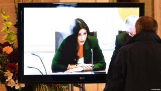 Man watches finance committee - chaired by Emma Little-Pengelly - on TV screen at Stormont, 23 August 2016