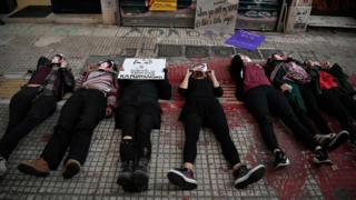 Activists lie down at the spot where activist Zak/Zackie was killed two month ago during a rally n Athens on November 24, 2018, marking the International day for elimination of violence against women