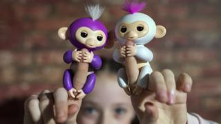 A girl holds up two 'Fingerlings',