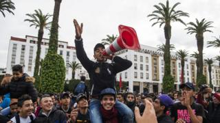 Moroccan students protest in front of the parliament - one holding a traffic cone - in Rabat, Morocco - Monday 12 November 2018