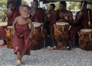 A boy dances as drummers in traditional dress perform at the Accra International Conference centre where the body of the late Kofi Annan has been laid in state in Accra, Ghana, 11 September 2018