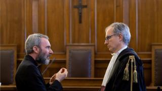 Father Carlo Alberto Capella, a Catholic priest sentenced to five years in jail for possessing child pornography, talks with his lawyer during a trial at the Vatican (June 23, 2018)