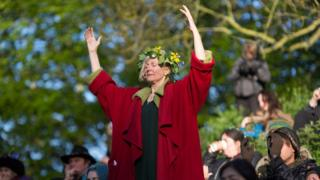 A woman taking part in a sun rise ceremony at Glastonbury Tor, Somerset