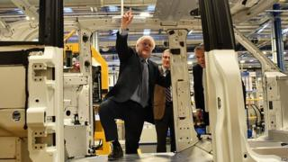 Boris Johnson inspects the frame of an electric taxi on a visit to the London Electric Vehicle Company near Coventry