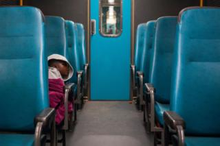 A kid sleeps in the economy class of the Shosholoza Meyl train on July 27, 2018 connecting Johannesburg to Musina
