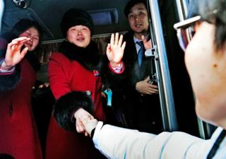 North Korean hockey players stand on a bus and wave farewell