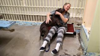 Inmate Kristina Hazelett plays with a dog in a cell