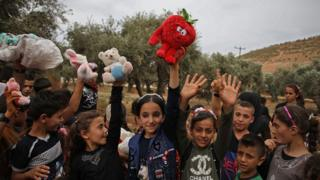 """Syrian children raise up toys that were given to them by a Syrian man living in Finland and calling himself """"The Toy Smuggler"""""""