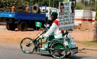 A supporter of President Muhammadu Buhari on a white and green painted tricycle in Abuja, Nigeria - Monday 6 February 2017