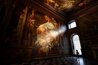 A gallery assistant poses beside a fresco during the reopening of The Painted Hall, Old Royal Navy College in London, Britain, 20 March 2019.