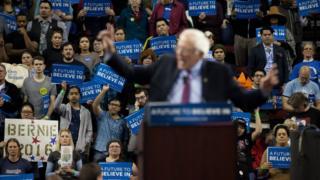 Bernie Sanders fans watch their candidate deliver a speech