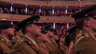 Poppies fell from the ceiling over members of the Royal Navy, the Army and Royal Air Force who stood in the centre of the hall