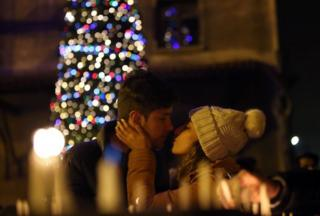 A couple kiss during a Christmas Eve ceremony at St Antuan Church in Istanbul, Turkey