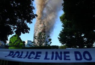 Cordón policial y la Torren Grenfell de fondo, envuelto en llamas y humo.