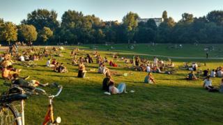 Pessoas tomam sol no parque