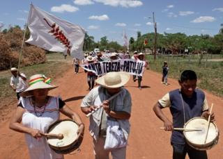 Protesters play instruments as they march to demand more action be taken to fight fires in Bolivia