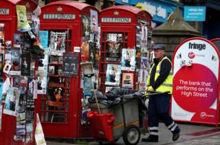 Street cleaner by flyposted phone boxes