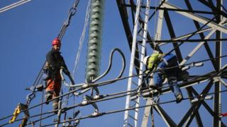 workers repairing electricity pylon