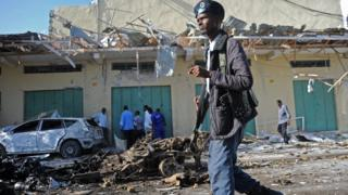 A member of the Somali security forces stands guard at the site of a bomb blast near Makka al-Mukarama Road in Mogadishu on December 19, 2015.