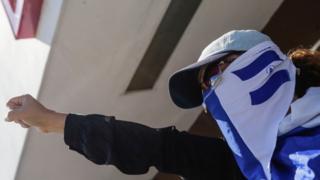 Mujer protestando con un pañuelo en la cara.