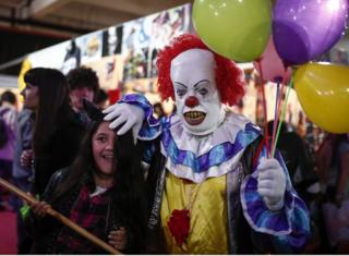 A man dressed as the clown from Stephen King's novel 'It' plays with a girl at the Anime Friends, a gaming and comic event in Buenos Aires, Argentina, on 24 July, 2016.