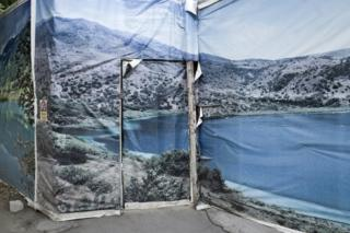 A photo of a poster of a scene of a lake in Kazakhstan plastered over a door