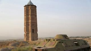 A destroyed Russian tank is seen alongside one of two minarets built in the 12th century in Ghazni city.