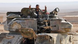 A soldier from the Syrian government forces flashes the 'V' for victory sign in the eastern Syrian city of Deir Ezzor during an operation against Islamic State (IS) group jihadists