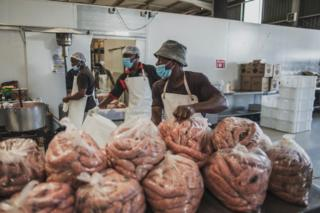 in_pictures Men in a kitchen in Johannesburg prepare large bags full of uncooked sausages.