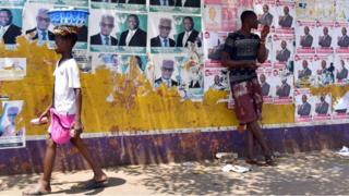 One man rest on top poster wall as e dey wait di result of di presidential election