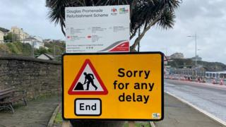 "DOI road works sign apologising for ""any delay"""