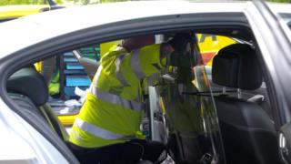 An AA engineer installing a perspex screen in a taxi